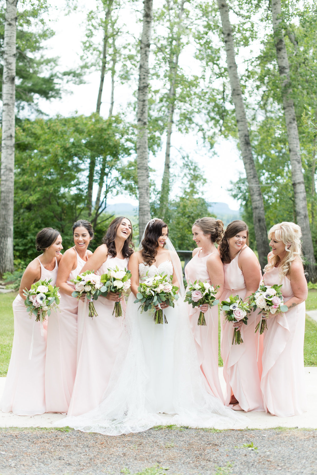 Bride and her bridesmaids wearing pink dresses and holding bouquets designed by Velvet Rope Floral during a summer wedding in Thunder Bay