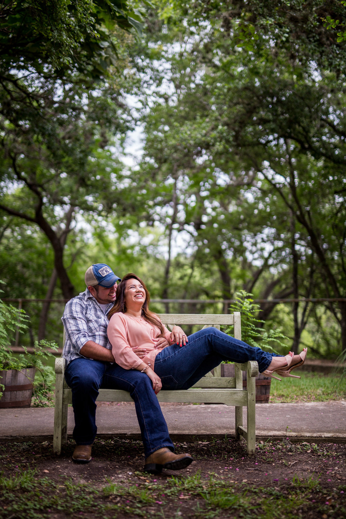 A man and woman in love and laughing while sitting on a bench in Gruene, Texas while on their engagement photo shoot.