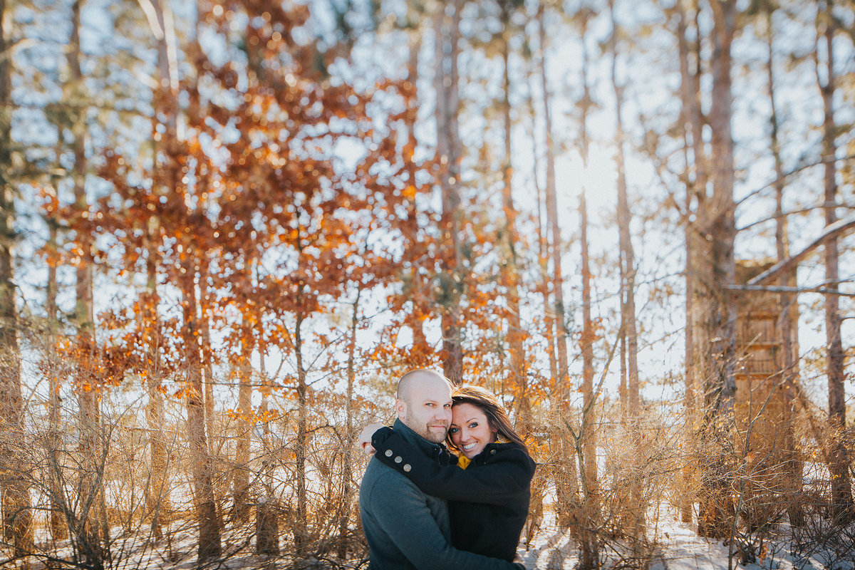 couple embracing during their winter engagement photography session at williams tree farm in rockton illinois