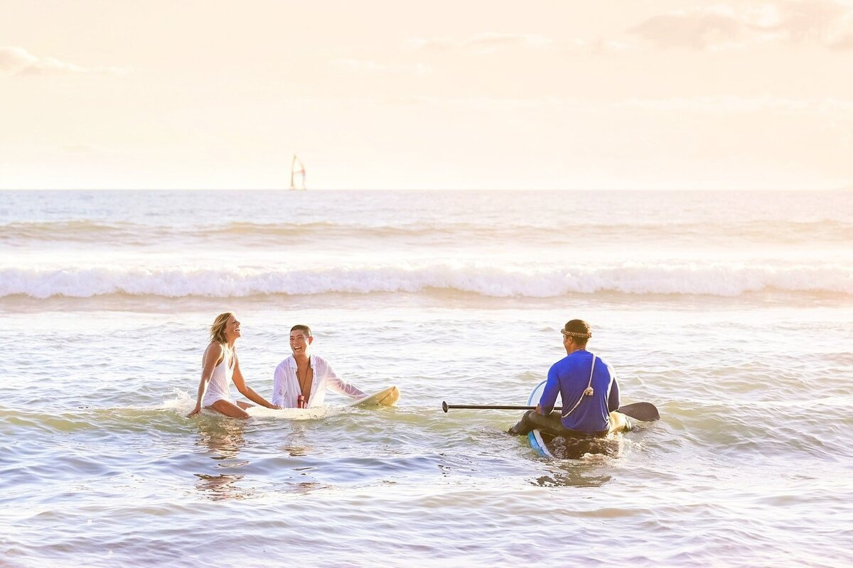 Bride and groom getting married on surfboards on Maui