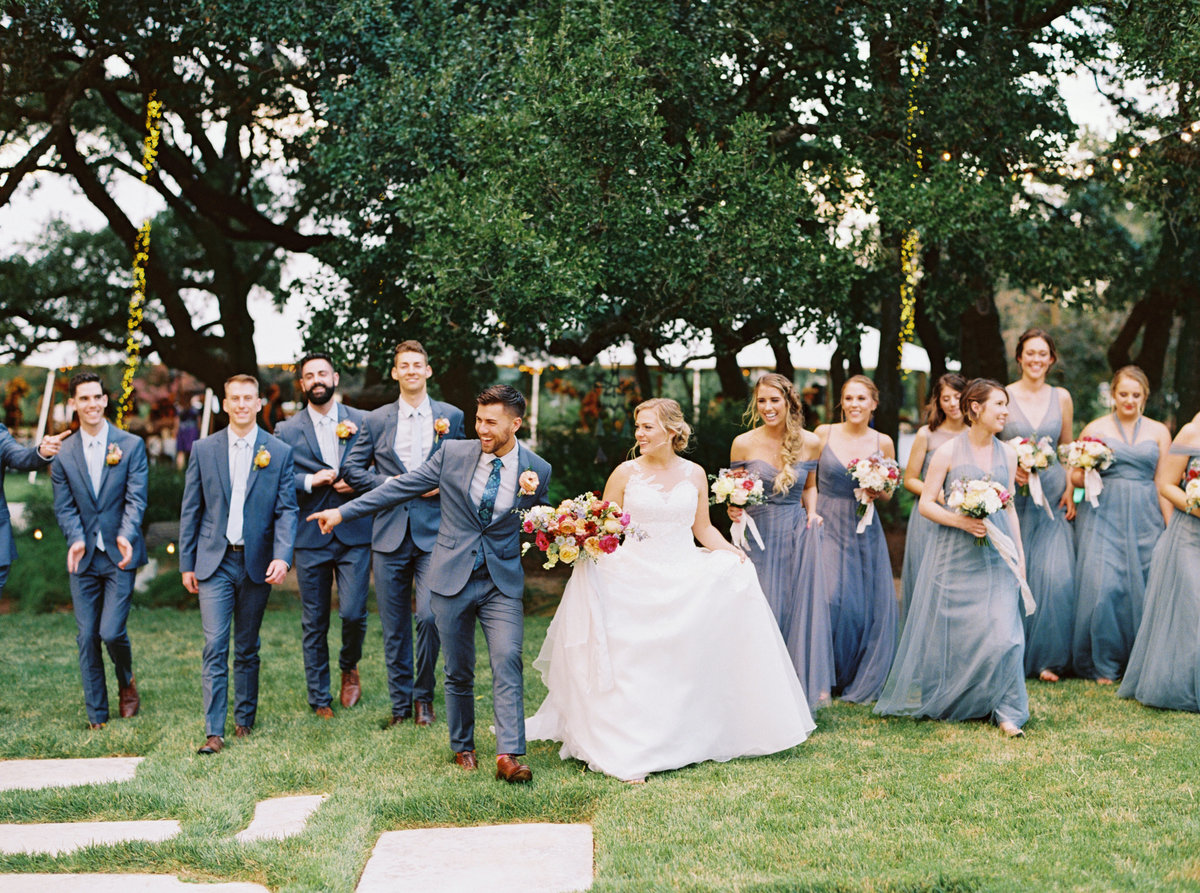 Bridal party smiling and walking