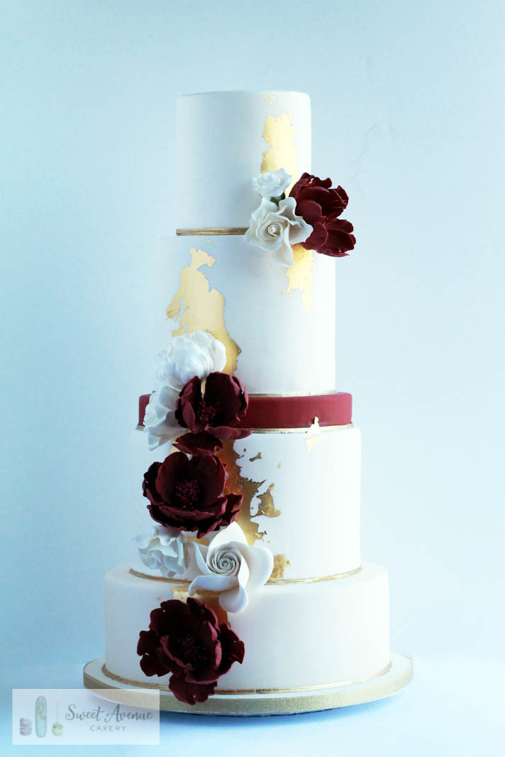 burgundy, white and gold modern wedding cake with gold leaf and flowers