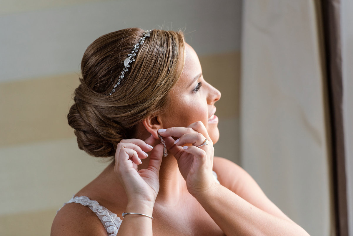 Bride putting in earrings at The Inn at Fox Hollow