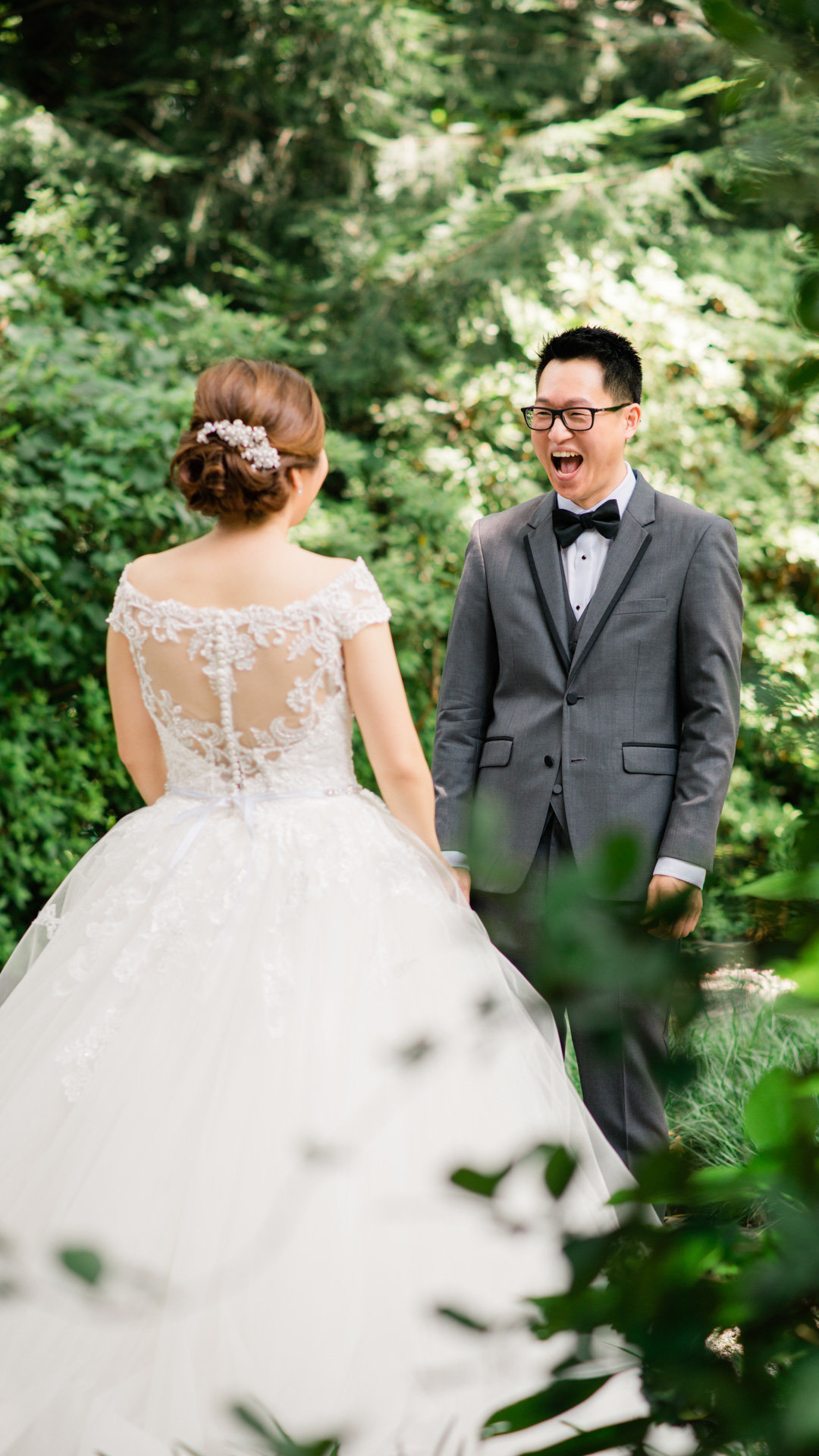 An emotional groom gasps at his bride during their first look