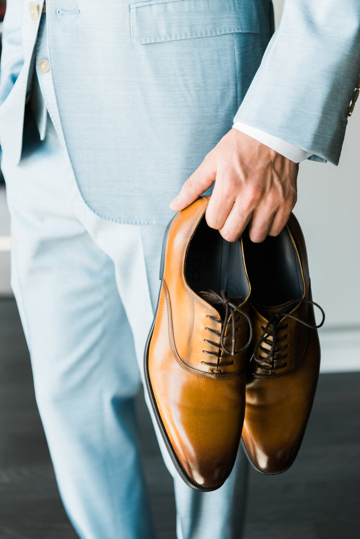 Groom holding brown leather shoes