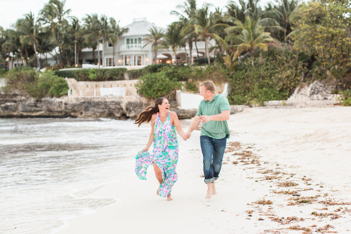 Couple running on the beach during engagement session