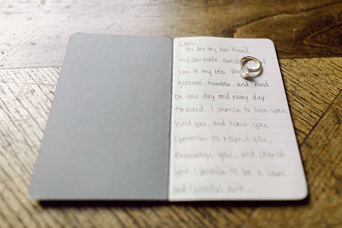 wedding vows written in small book with engagement ring sitting on top