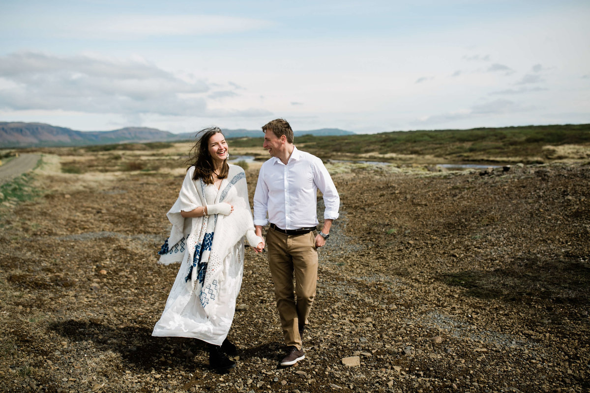 laughing, the couple holds hand in a valley in iceland.