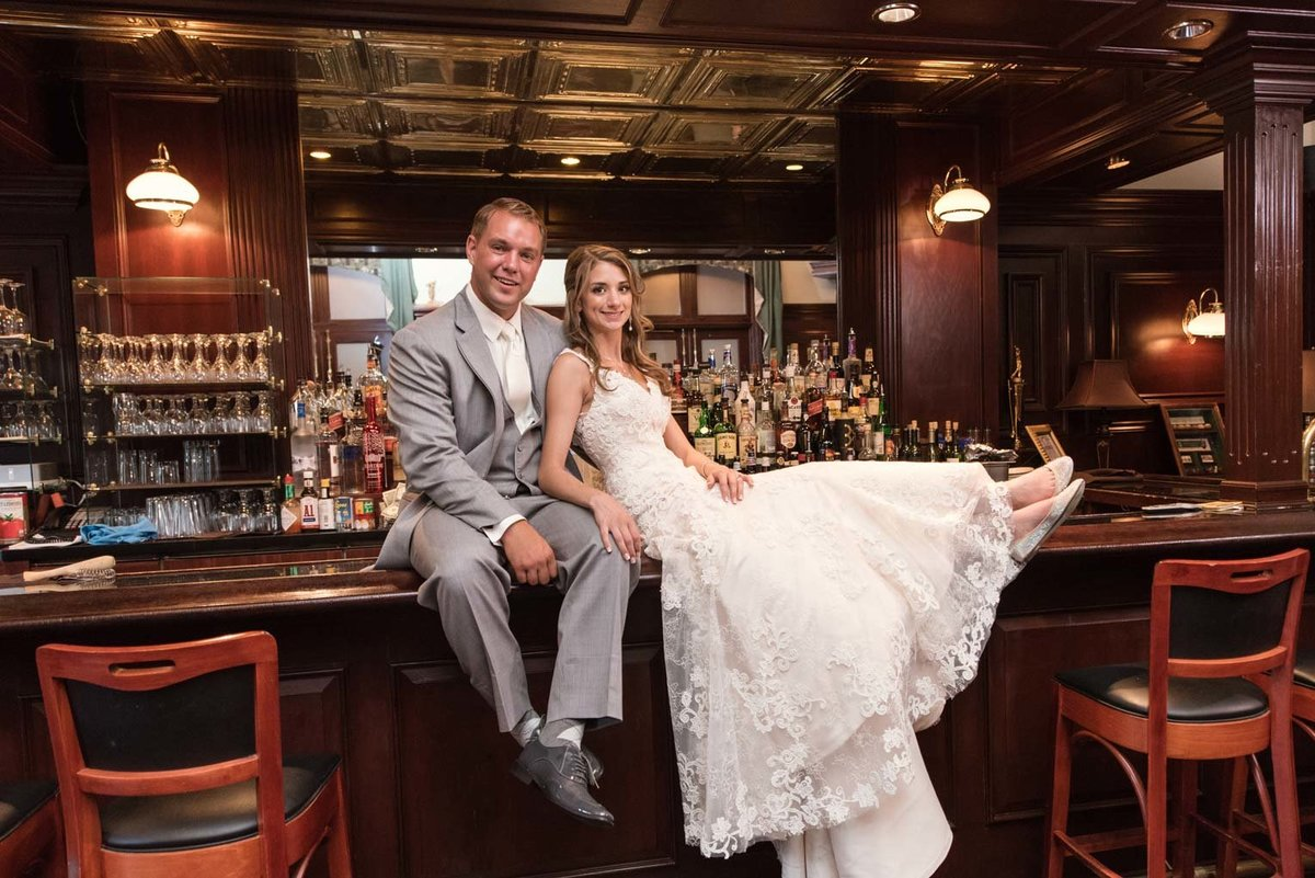 Bride and groom on the bar at The Mansion at Oyster Bay
