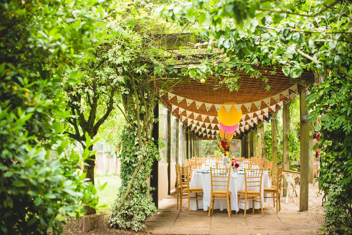 an outdoor wedding breakfast with bunting and paper lanters at maunsel house