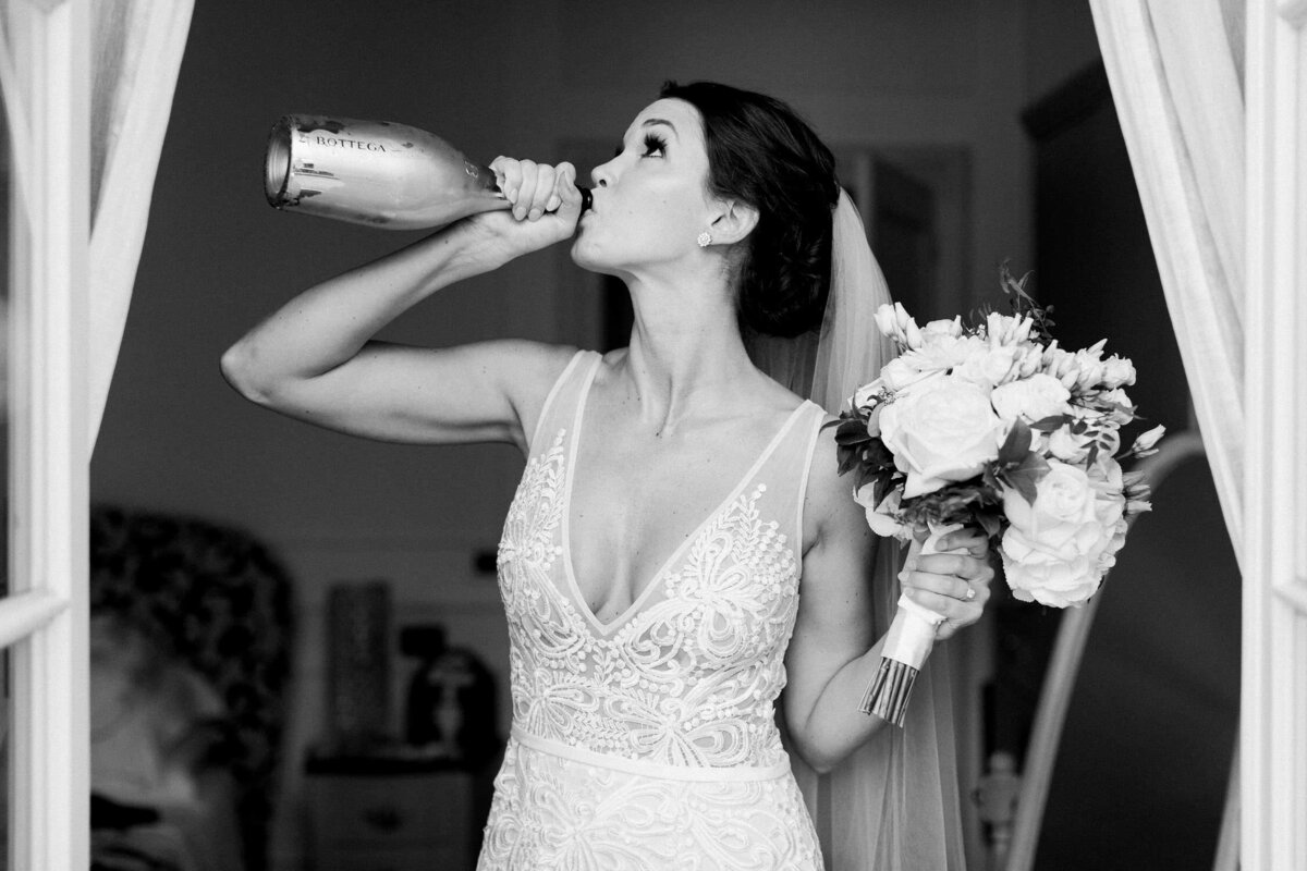 Bride holding floral bouquet and drinking bottle of wine in white lace wedding dress against black background
