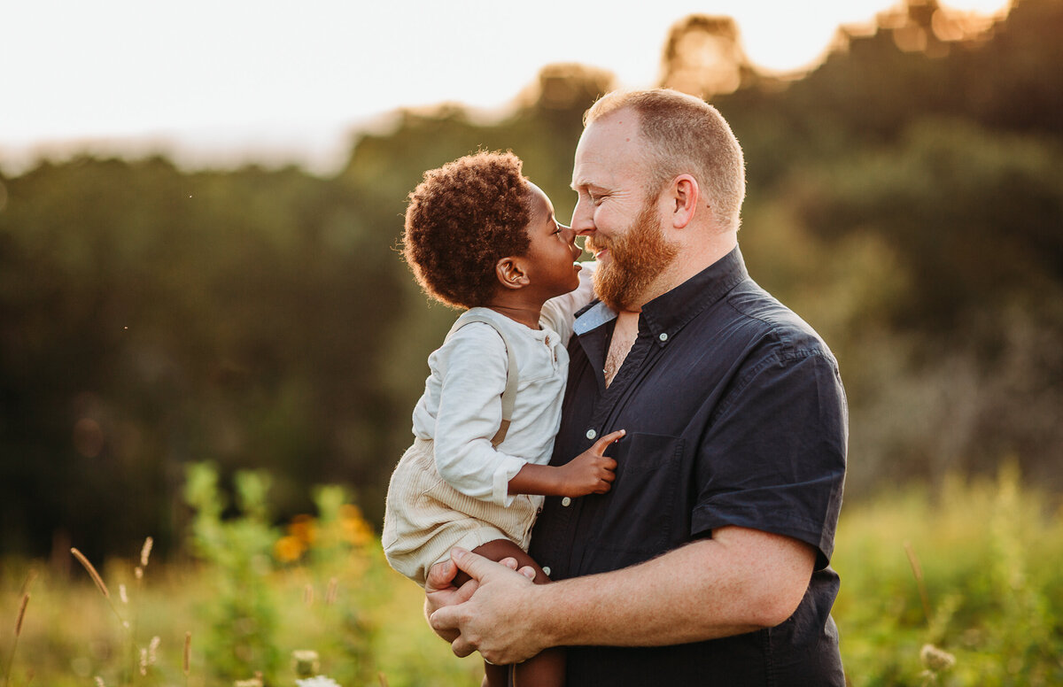 father holds adoptive son nose to nose during boston family photography session