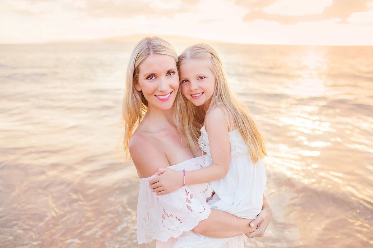 Mom and girl look at the camera during their portrait session at the beach