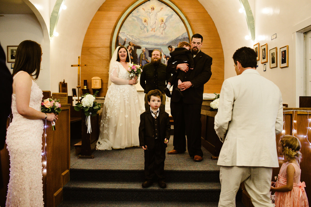 ring bearer stands in the middle of chapel in seward with chaos around