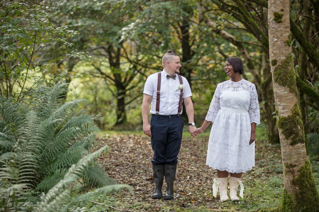 Bride in wellington boots holding hands with groom at elopement wedding The Green Cornwall