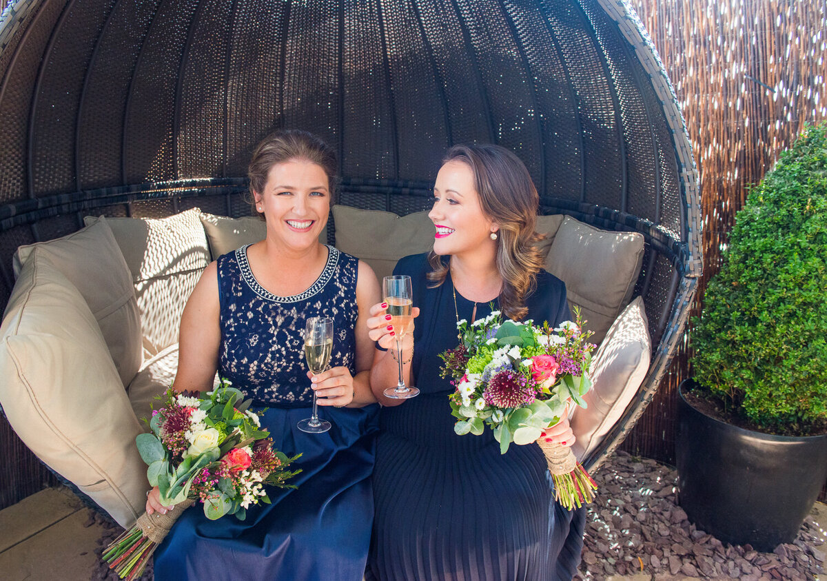 Gay brides wearing blue dresses, with champagne and colourful flower bouquets