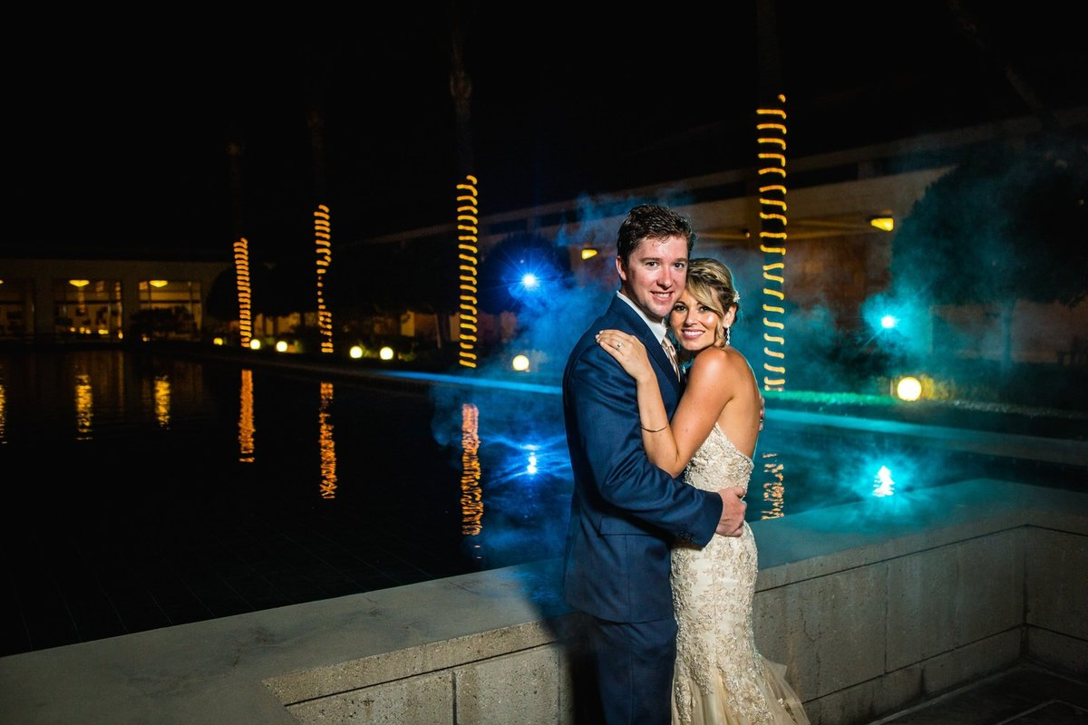 Bride and Groom embrace for a night shot at the Richard Nixon Library with colored lighting in the background