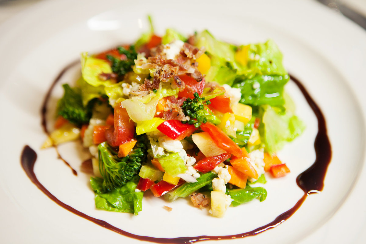 Vizcaya Chop Salad seasonal vegetables, shaft blue cheese, bacon, & balsamic vinaigrette.