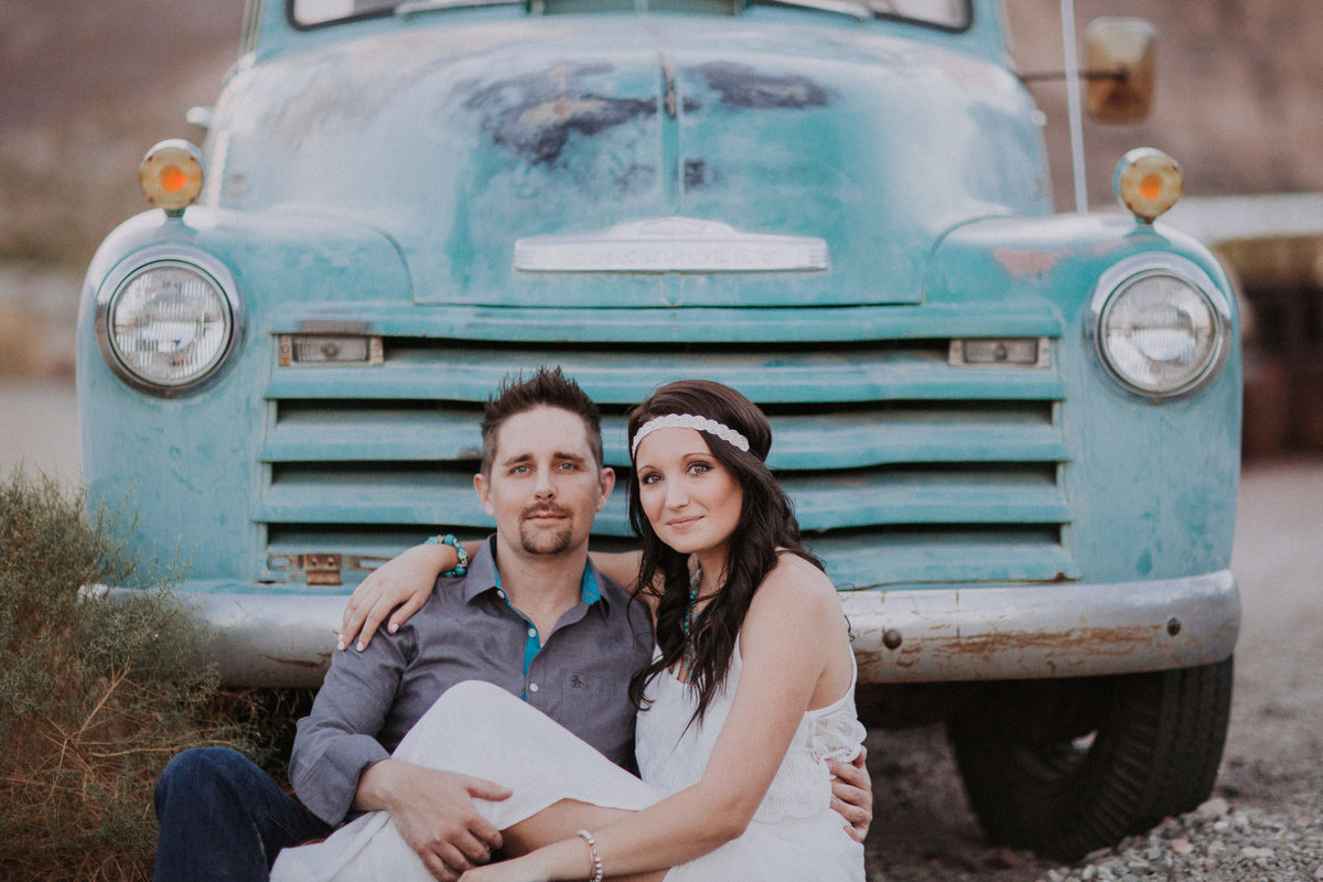 Lake Tahoe engagement pictures couple sits in front of vintage teal truck