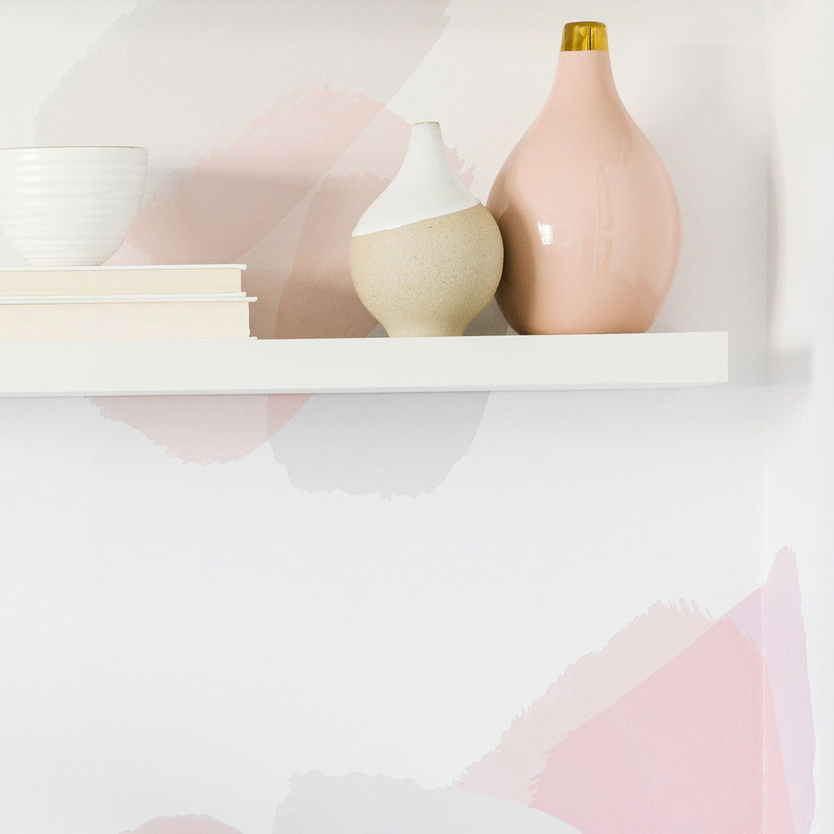 Office shelf with accessories on white and pink wallpapered wall