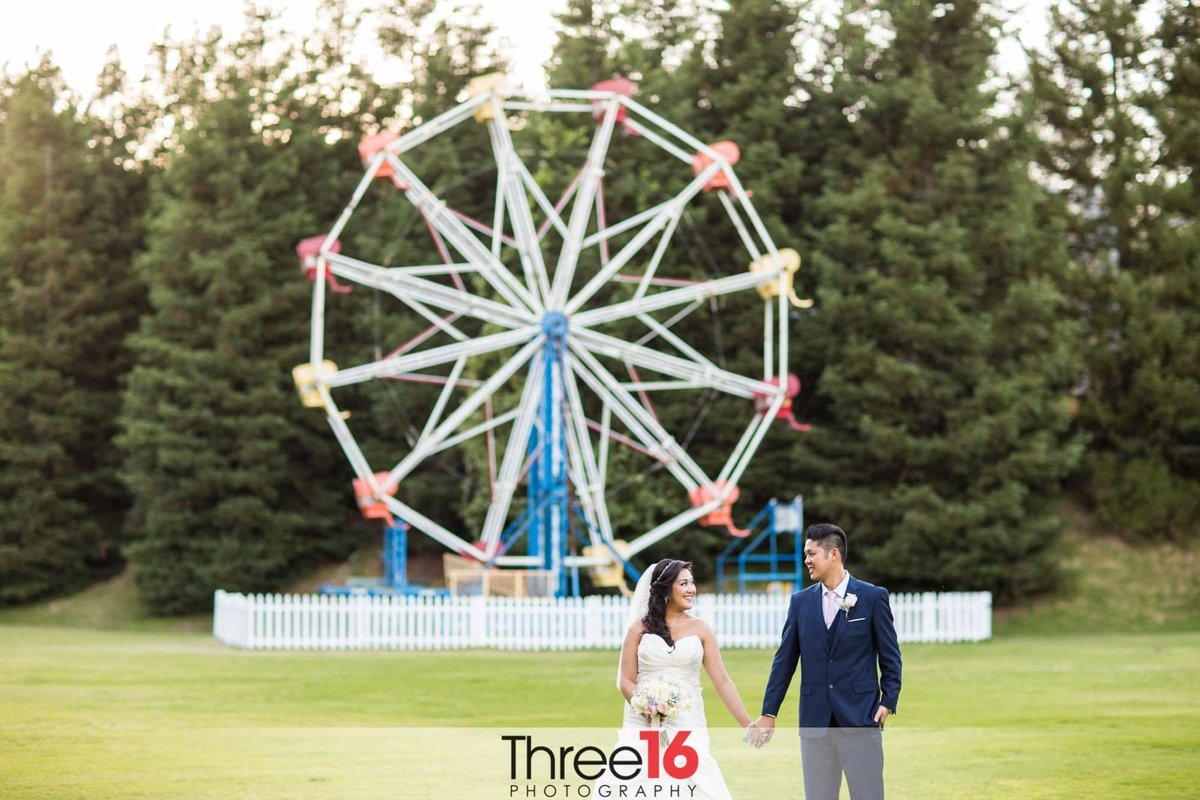 Bride and Groom hold hands and look at each other in front of the Calamigos Ranch Ferris Wheel