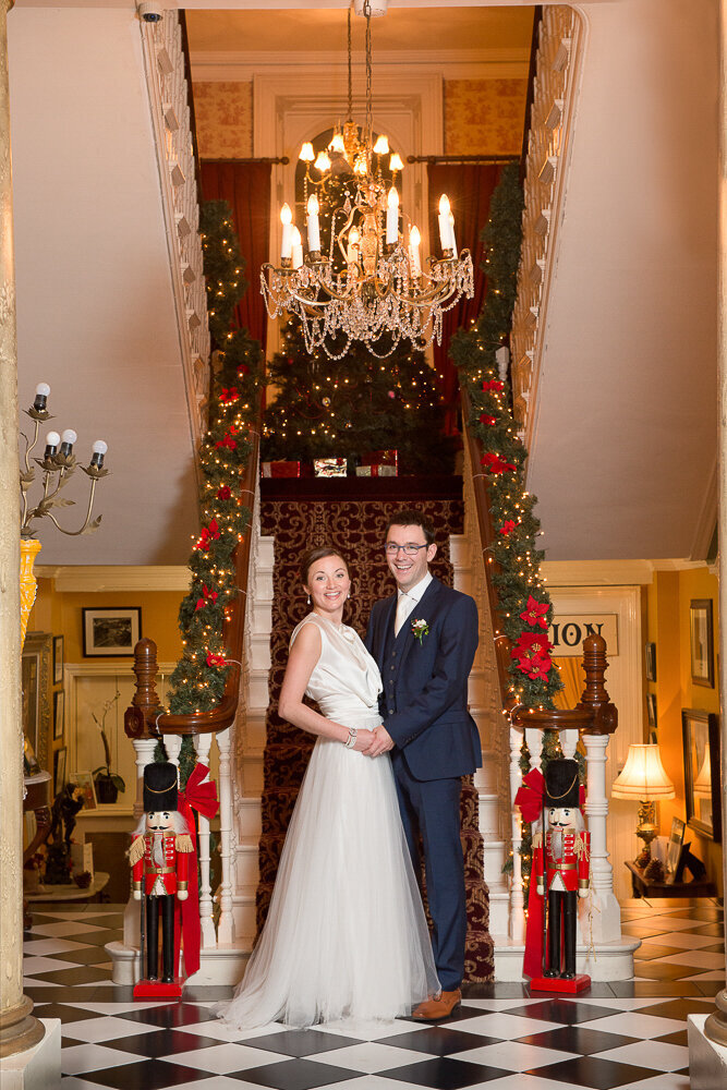 brunette bride wearing an a-line, tulle wedding dress with groom wearing a navy suit standing at the bottom of the stairs of Ballyseede Castle decorated for Christmas