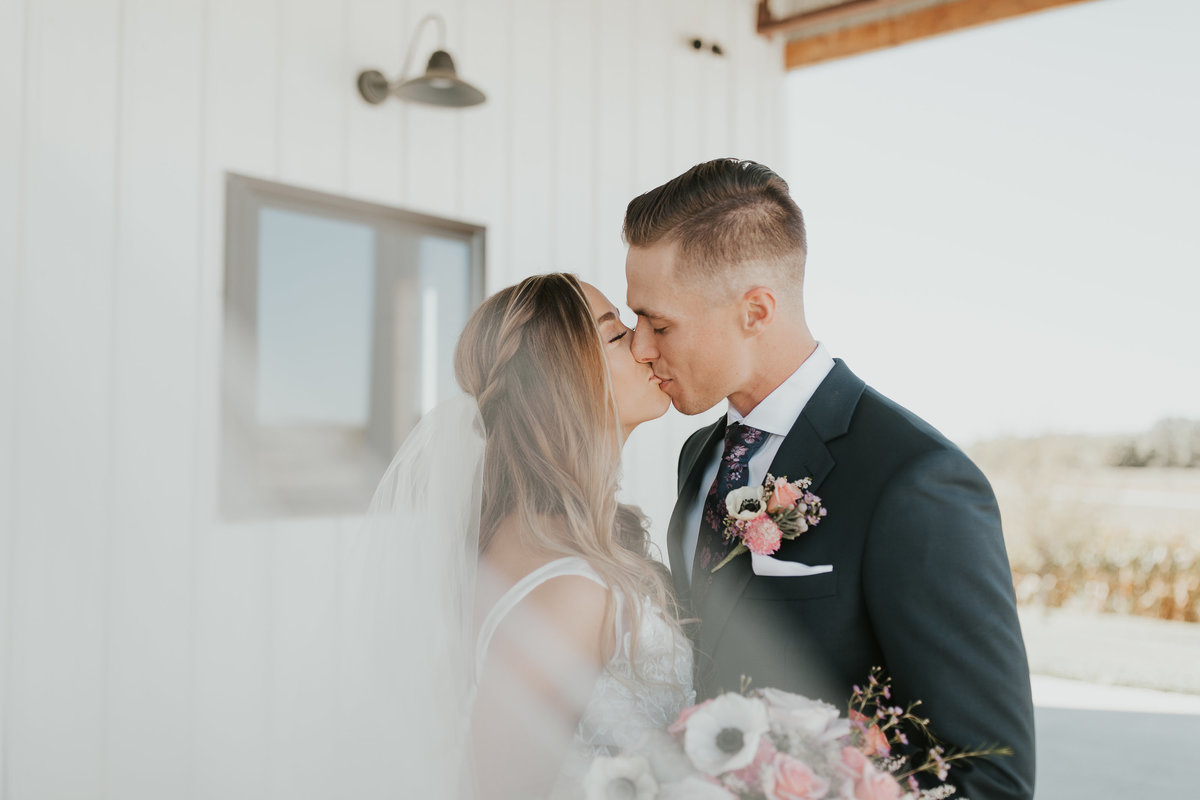 Bride and Groom kissing during their Romantic Wedding at Wishing Hills Barn in Missouri Valley, Iowa