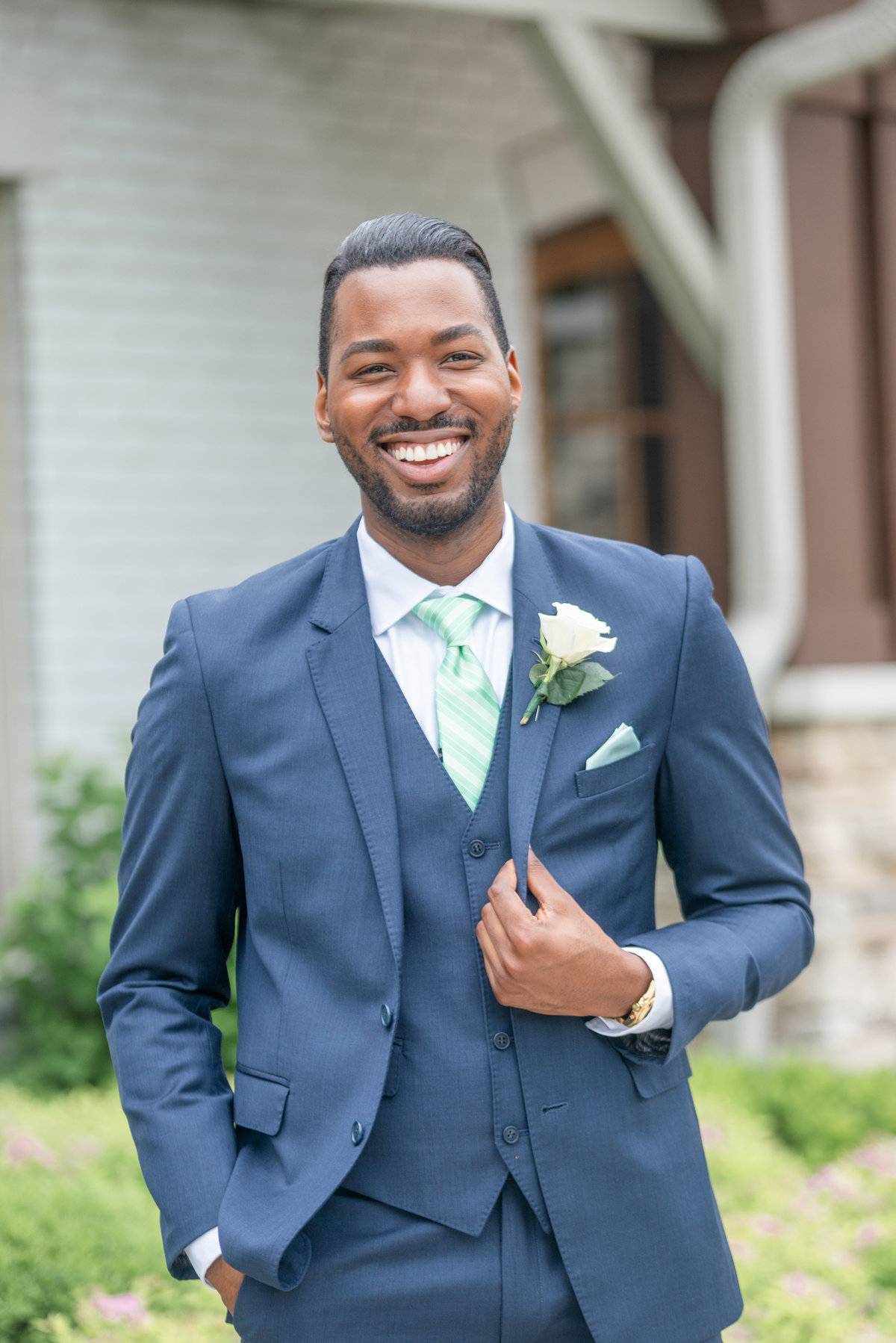 Stylish groom smiles while wearing a dark blue suit and green tie