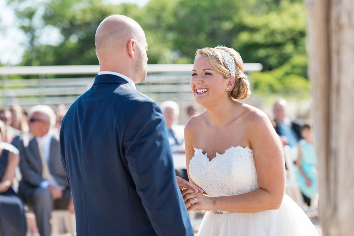 bride smiling at groom during wedding ceremony on the beach at Pavilion at Sunken Meadow