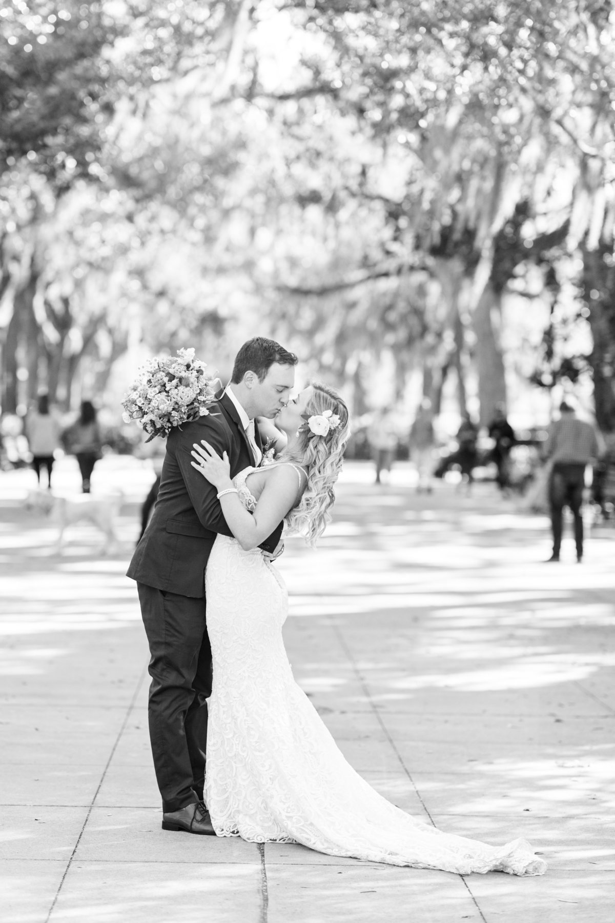 black and white image of bride and groom embracing and kissing
