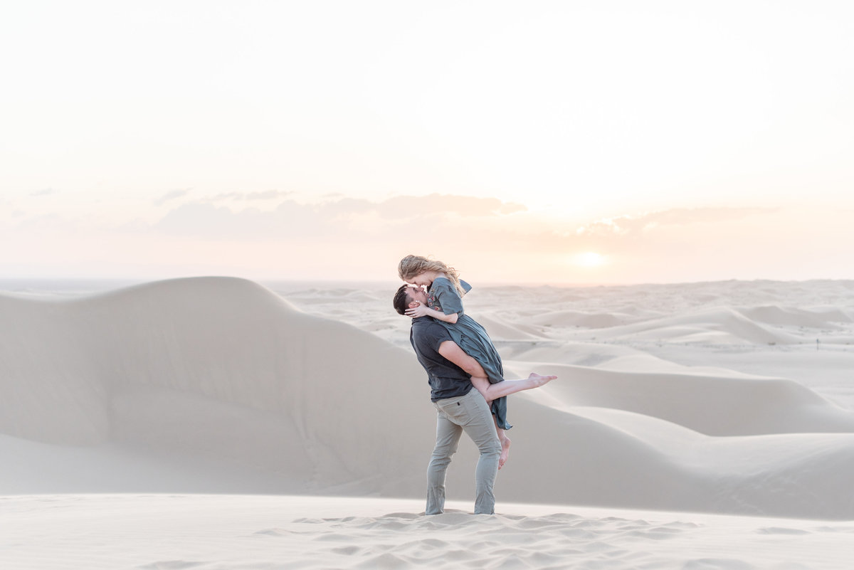 groom lifts bride and kisses her at glamis sand dunes