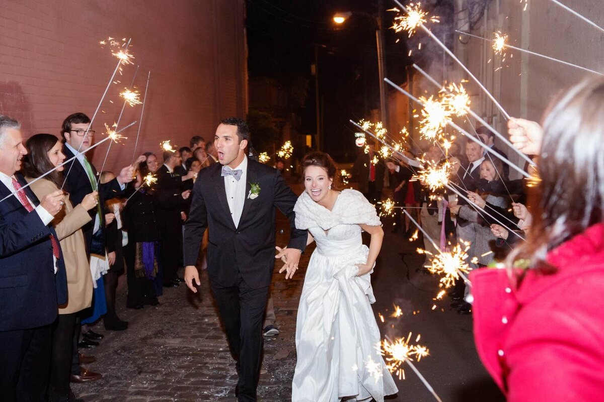 a happy couple exit their wedding surrounded by sparklers