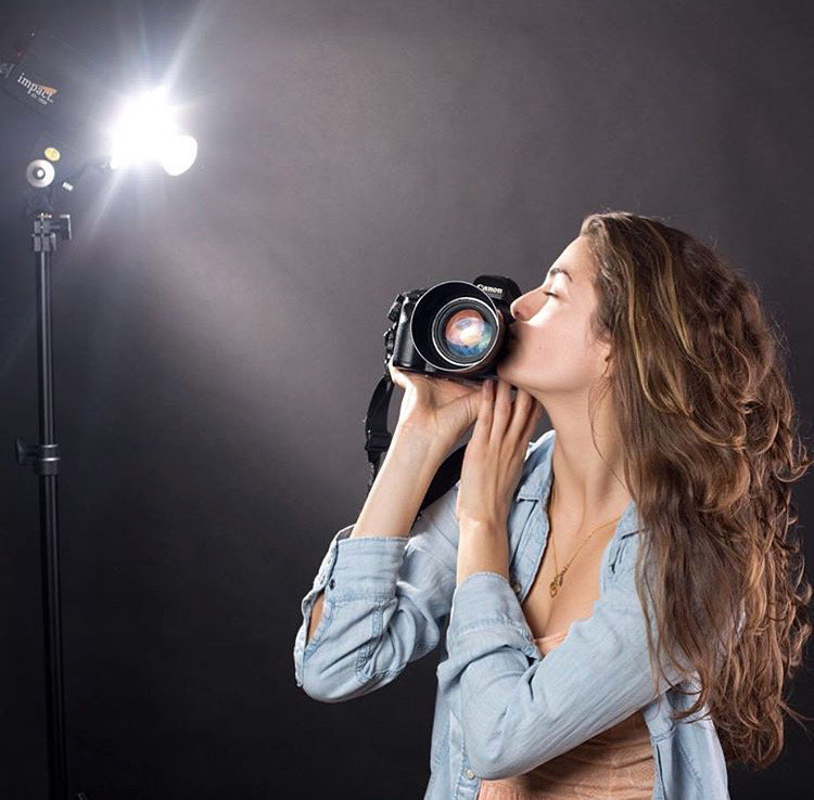 Laura Volpacchio kisses her camera in NYC photography studio.