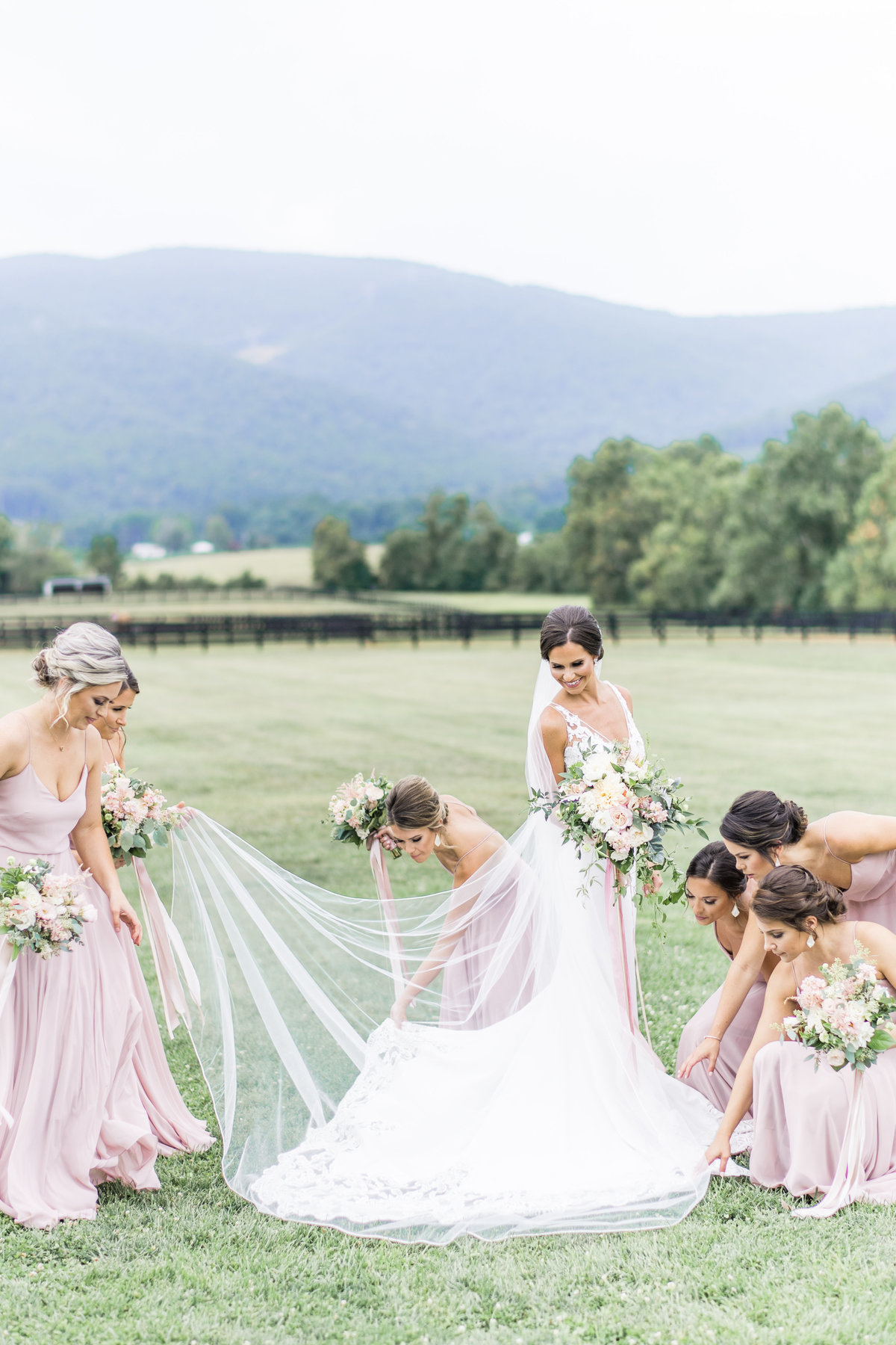 Bridal party helping the bride fix her dress at King Family Vineyards, Virginia.