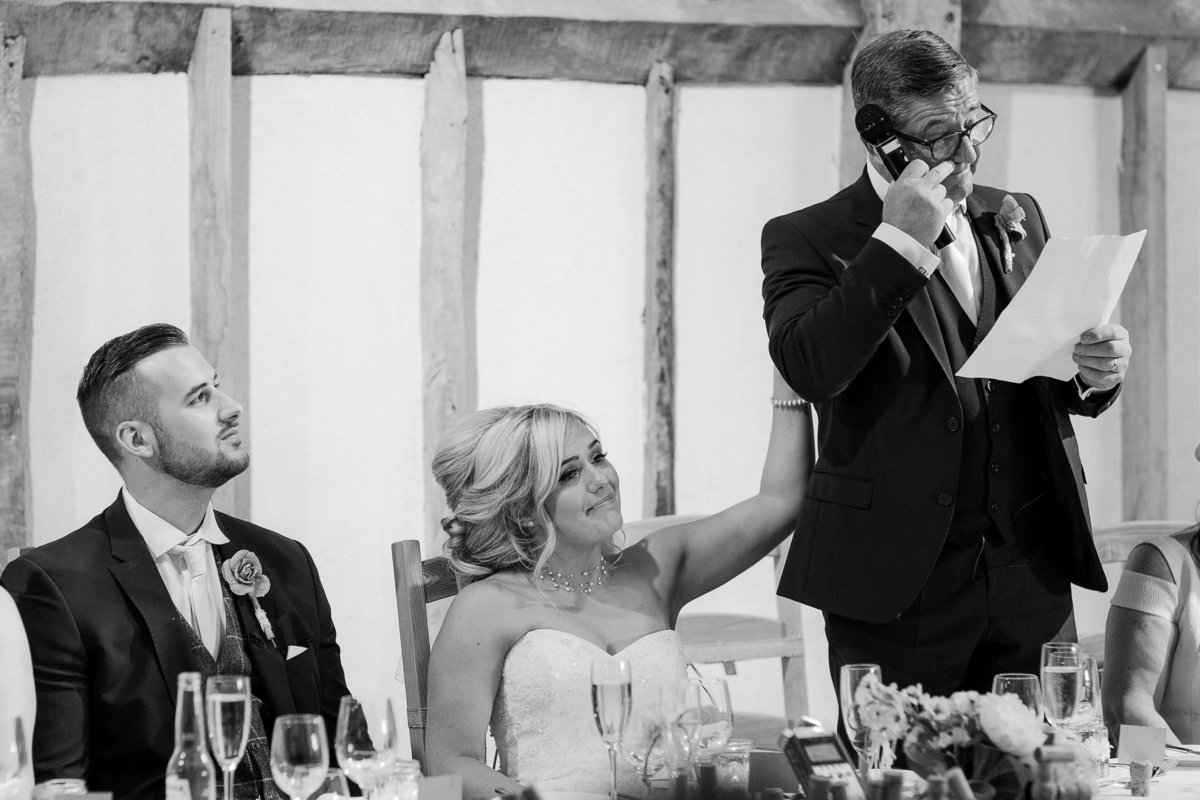 Father of the bride gets emotional during his speech at his daughters Southend Barns wedding  and the bride comforts him with a hand on his back as the groom watches on