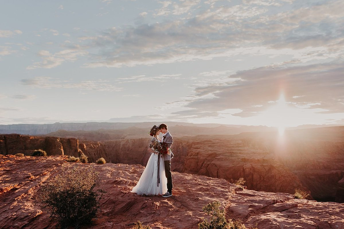 bride and groom embrace while horseshoe bend is behind them