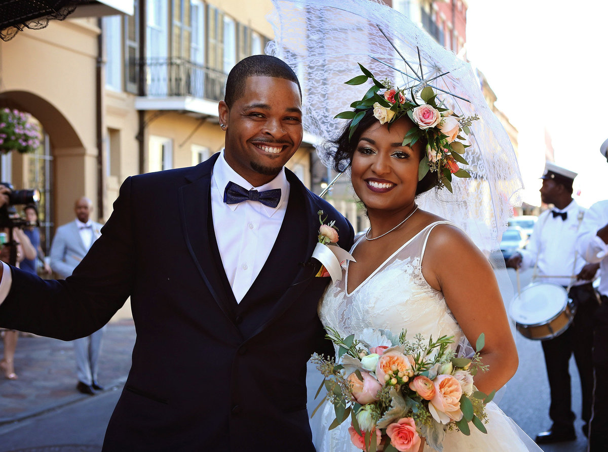 closeup of bride and groom in front of Chateau LeMoyne Hotel