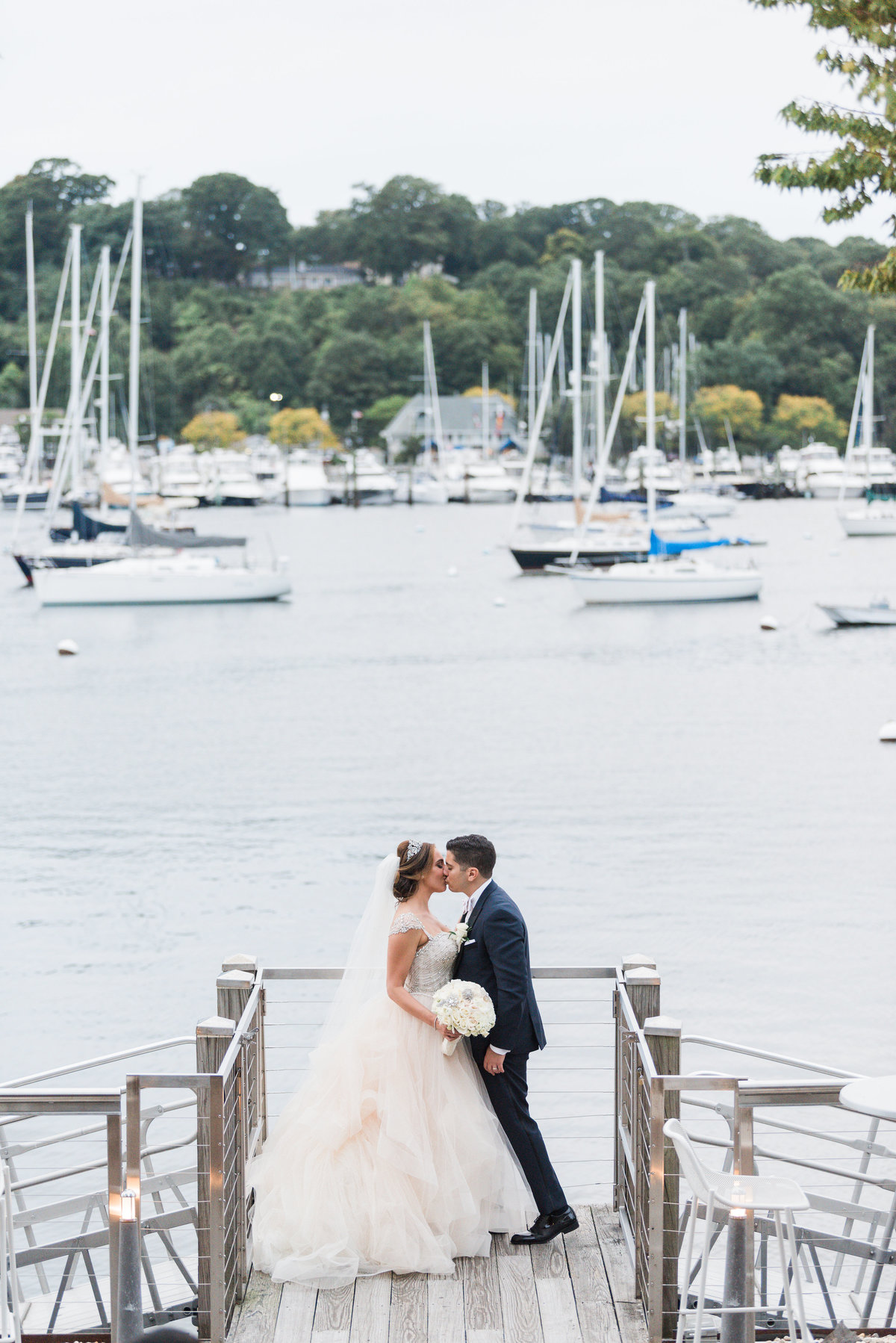Bride and groom kissing at the dock at Prime