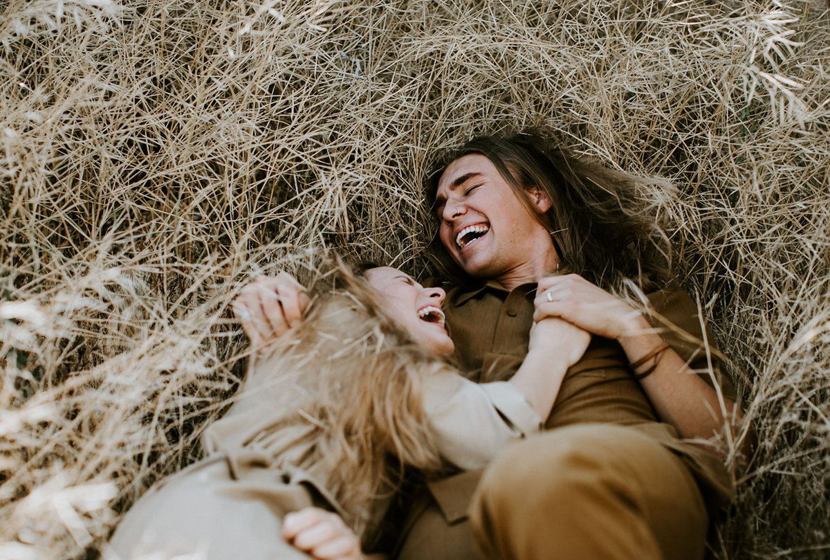 A man and woman lay in a field and laugh.