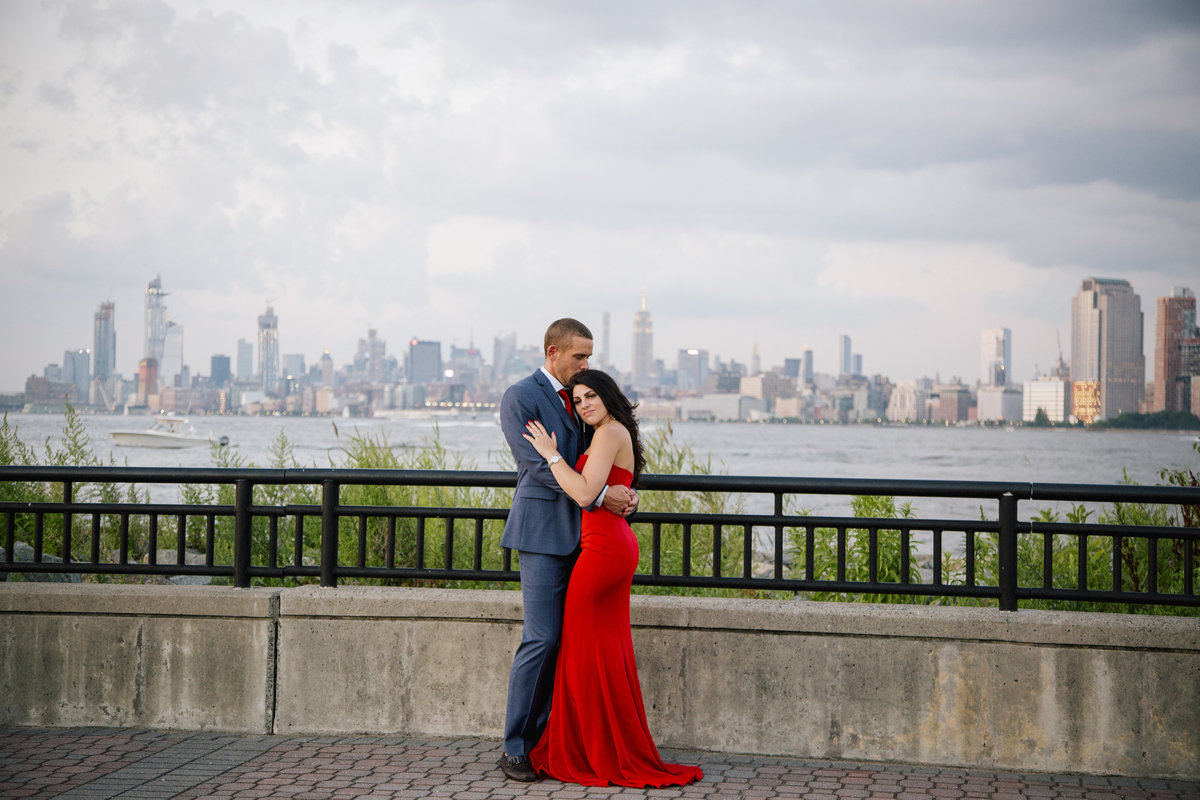 engaged couple hug by nyc skyline  at liberty state park