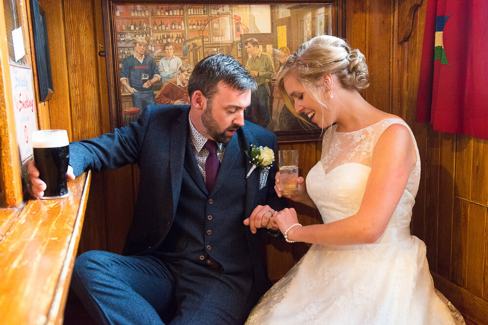Bride with blonde hair, wearing a princess style wedding dress sitting in the snug in Dick Mack's pub with her groom, wearing a navy suit and waistcoat with wine tie, holding a Guinness and looking at the wedding rings
