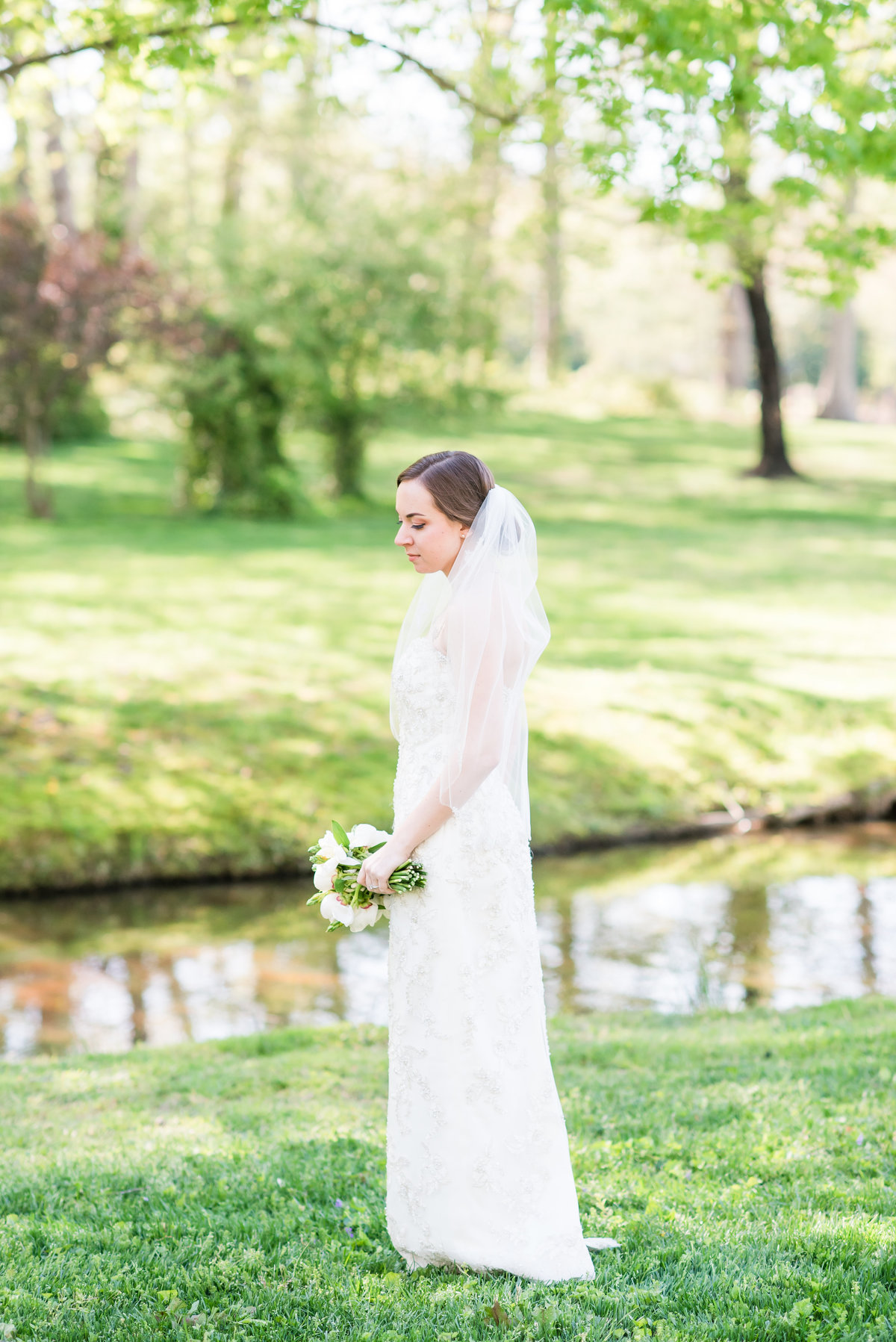 a bride wearing a laced strapless dress with no train with a mid-length veil standing in front of a pond looking down holding a white and green wedding bouquet in early spring in Burlington NC