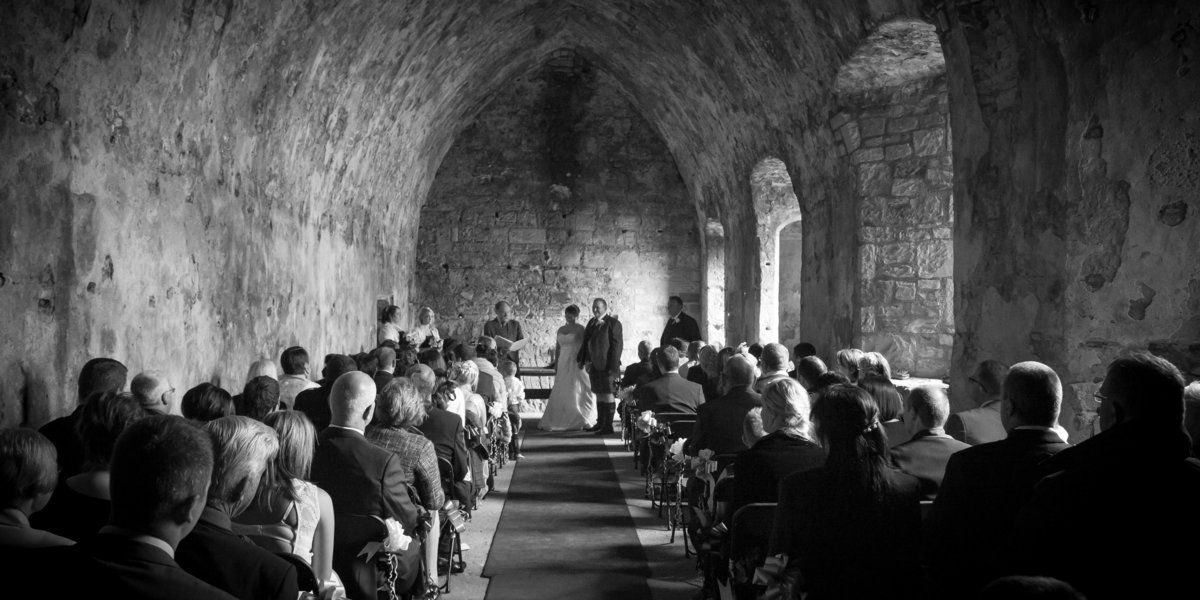 Black and white photograph during a wedding ceremony in an old vaulted abbey