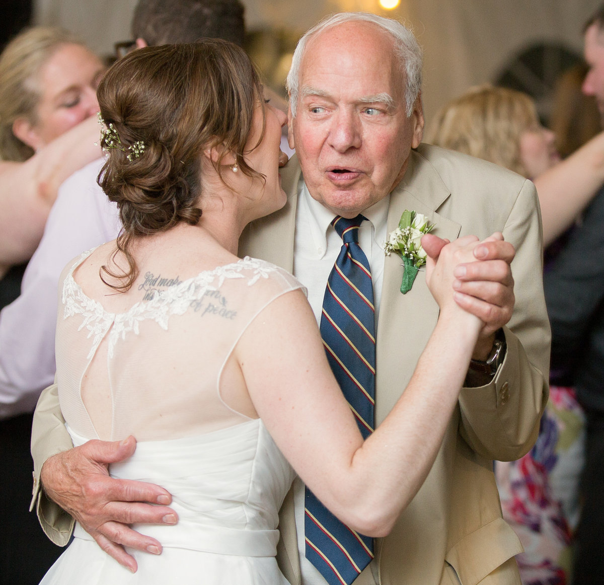 Bride is laughing while dancing with her father in law at National Aviary wedding reception