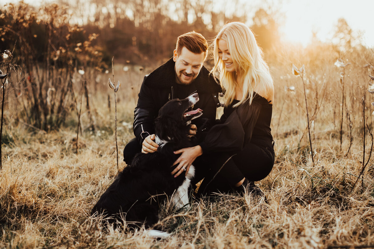 couple petting their dog in grass at sunset