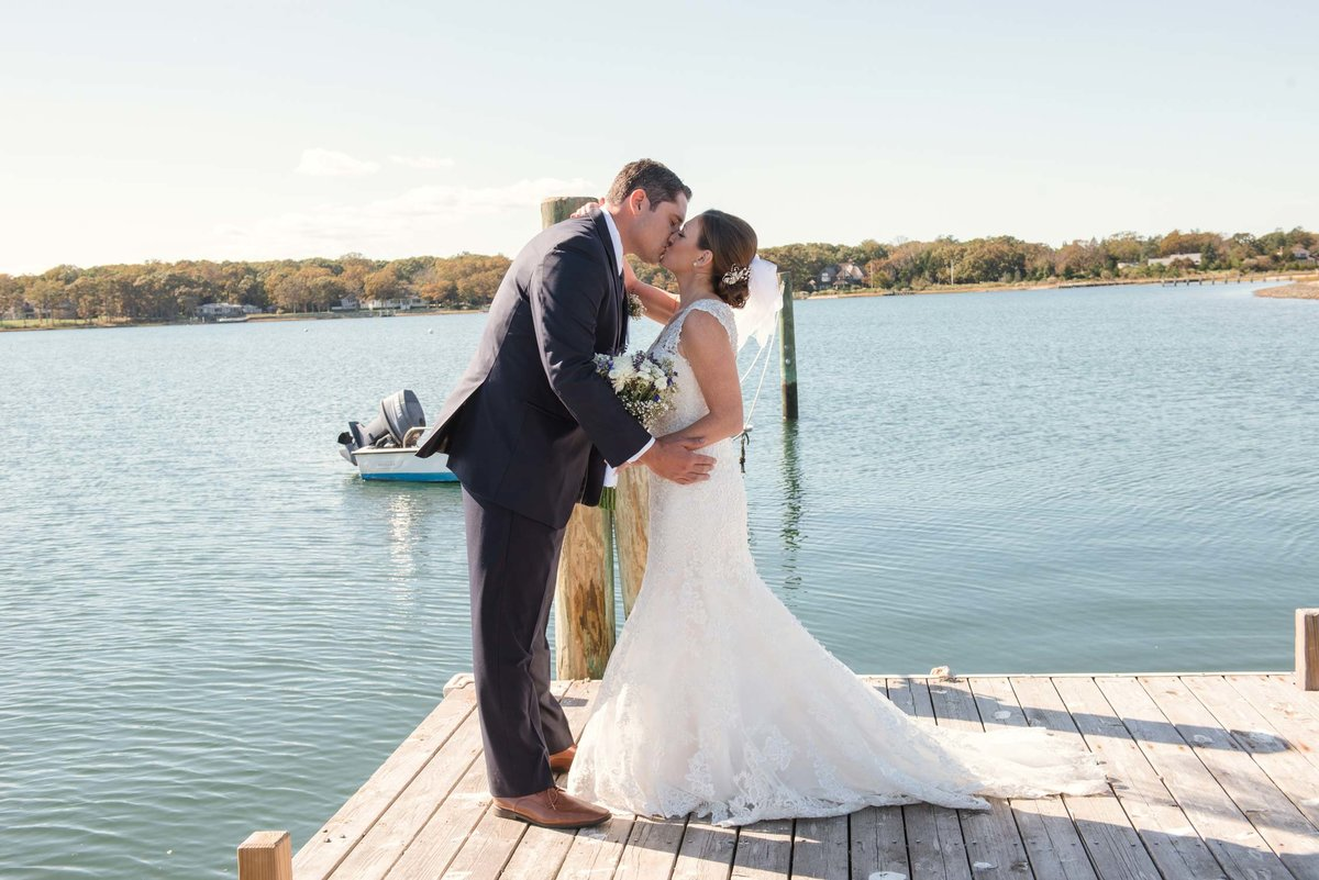 Bride and groom kissing on dock at The Ram's Head Inn