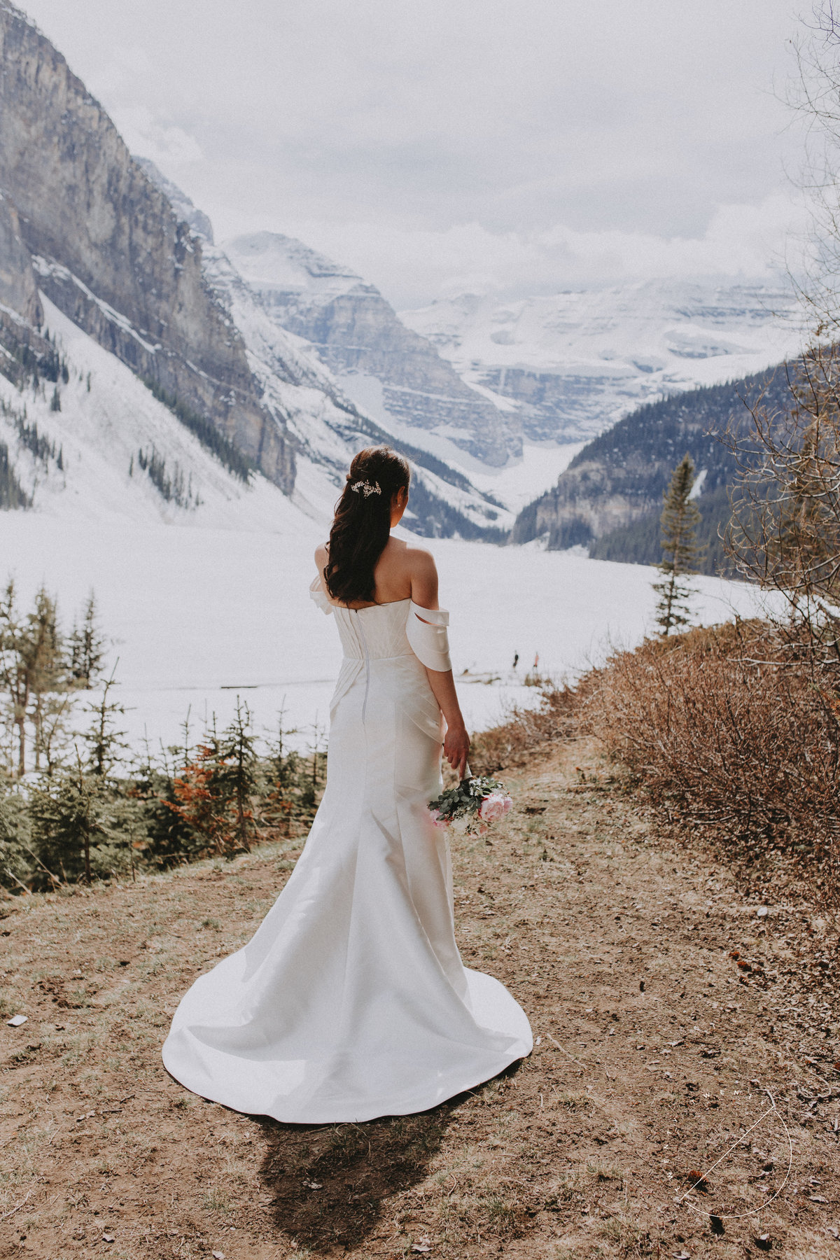 Bride looking out at Lake Louise after their May wedding Ceremony in front of Chateau Lake Louise
