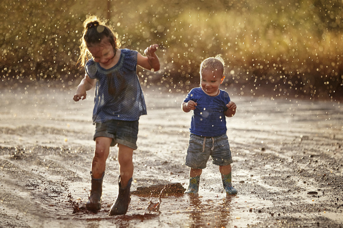 Young girl and boy in wellington boots splashing in puddles with rain falling down on them