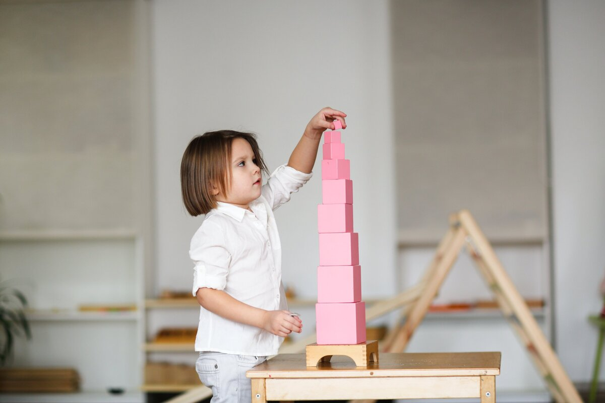 child-girl-playing-with-pink-tower-developing-sensory-activities-in-montessori-and-earlier-child_t20_ZY7z1a