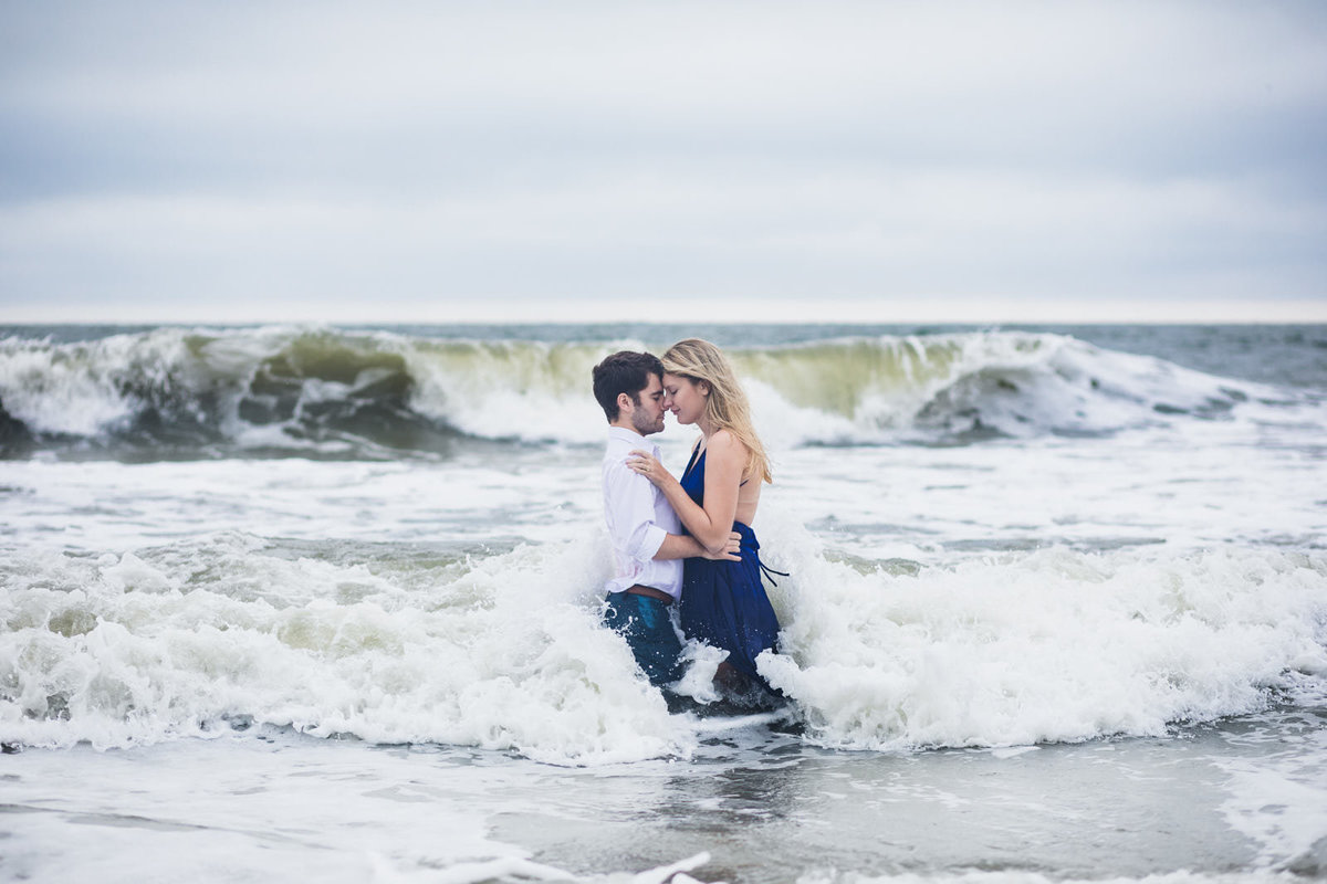 couple kisses in ocean for engagement portrait at Tybee Island beach